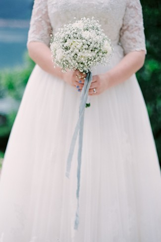 Bride holding a bouquet of white baby's breath with a blue ribbon created by Figli Dei Fiori