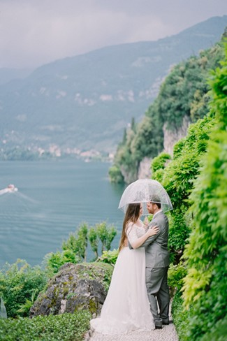Bride and groom embracing at Villa Del Balbianello under a clear umbrella