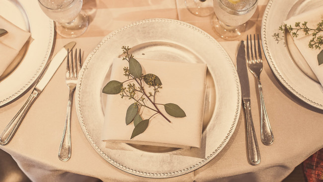 table setting with greenery on white napkin