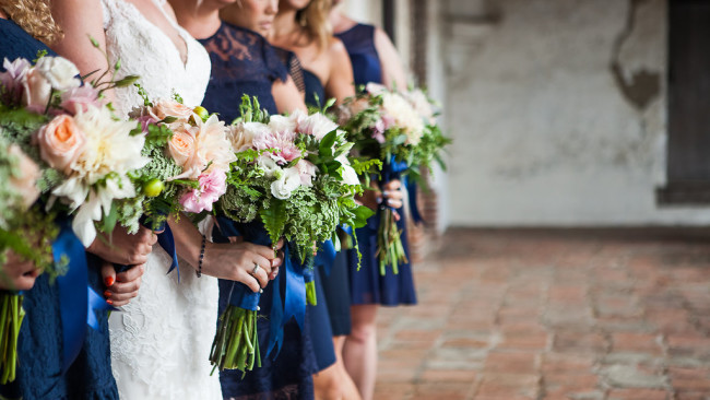 row of bridesmaids holding flower bouquets