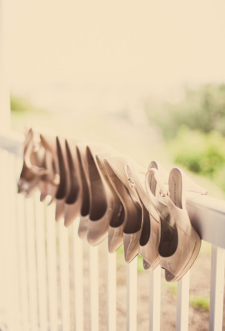 bridal shoes hanging in a row on banister