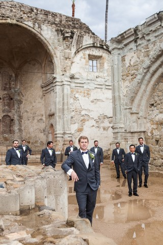 groom and groomsmen in suits standing at ruins of Serra Plaza
