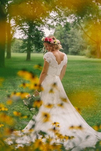 Bride standing in front of yellow flowers with her train spread out