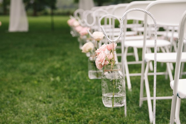 Outdoor wedding ceremony aisle with hooks and hanging mason jars with pink roses