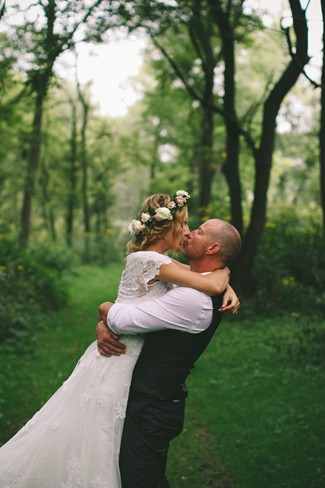 Bride and groom kissing in the forest in Iowa captured by Rachel Zierke Photography