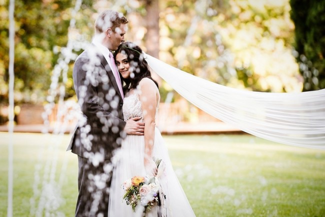 Newlywed couple embracing with bride's veil blowing in the wind