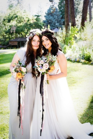 Bohemian bride standing with bridesmaid wearing flowers in their hair and holding bouquet with loose ribbon