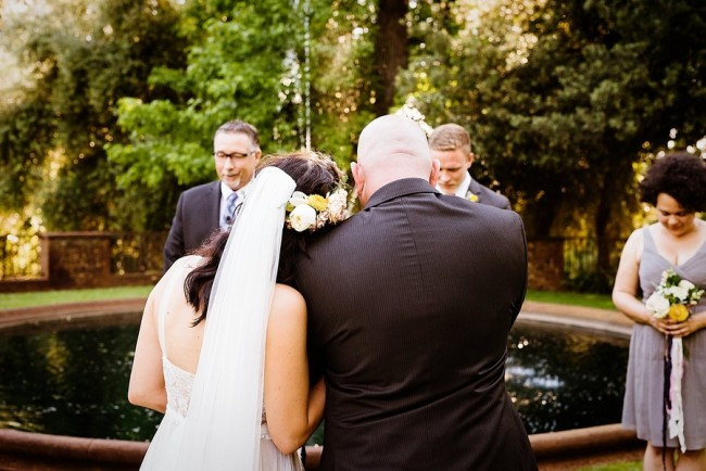 Bride and groom head to head during prayer at outdoor wedding ceremony in California