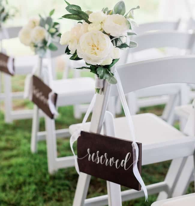 wood reserved seating sign hanging on white chair