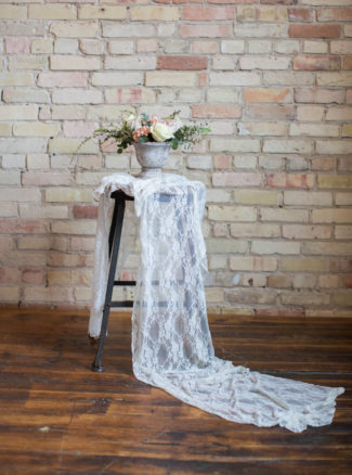 lace table runner against brick wall