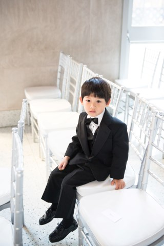 Little ring bearer wearing a black tux waiting for the wedding ceremony to begin