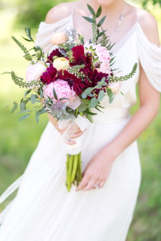 Bride holding a beautiful deep red, pink and green bouquet from Endless Creations Flowers