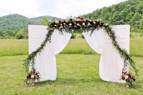 Ceremony altar with white doors and cloth, green foliage and deep red florals