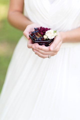 Bride holding little pot of blue berries and white and red flowers