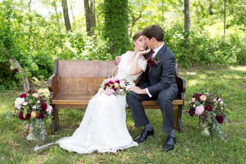 Bride and groom sitting on a wood bench at Ducard Vineyards