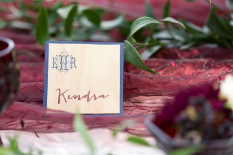 wood place card with red and blue writing