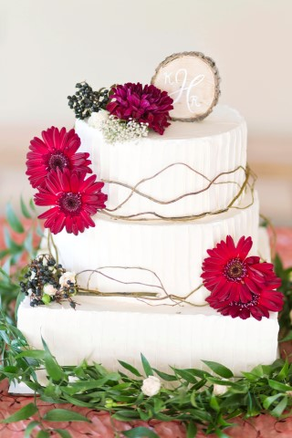 3 tier white wedding cake with pink Gerber daisy created by Heavenly Scent Cupcakes & Cakes