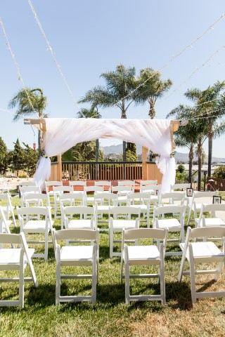 Backyard wedding with white fold up chairs