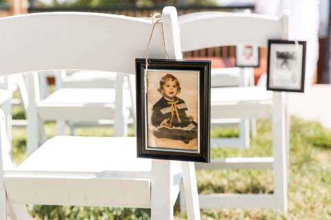 Outdoor wedding ceremony decor with bride and grooms picture as babies