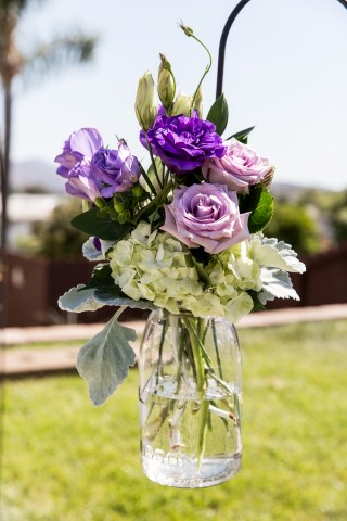 Purple flowers with white hydrangeas in a clear jar for wedding decor