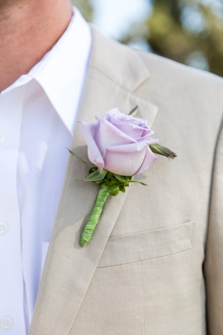 Groom wearing a purple rose boutonniere