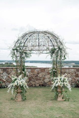 Rod Iron ornate domed wedding altar decorated with white flowers
