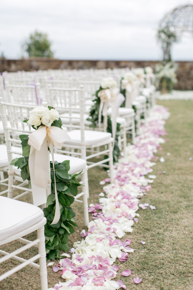 Outdoor wedding ceremony with white chevalier chairs and aisle lined with pink and white rose petals