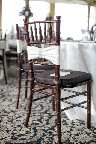 Brown chevalier chairs wrapped with a white silk ribbon