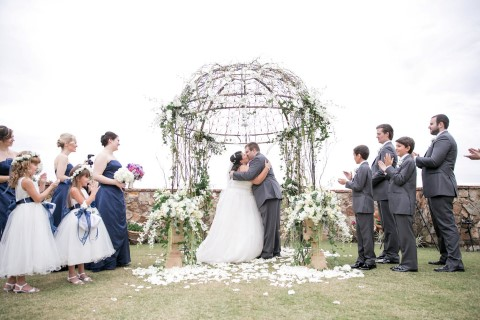 Bride and groom kissing during wedding ceremony at Bella Collina