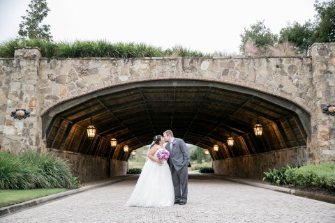 Bride and groom kissing under bridge at Bella Collina