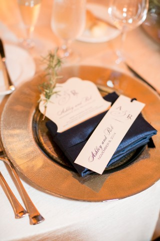 Gold chargers with navy blue folded napkins for wedding reception decor