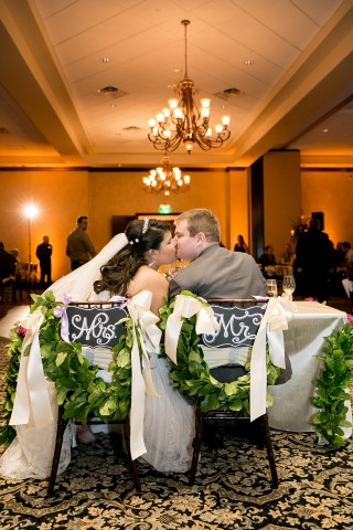 Bride and groom kissing while sitting in their reception chairs with Mrs and Mrs chalkboard signs