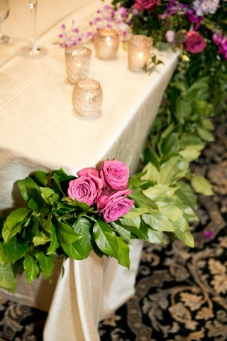 Green foliage with purple roses for wedding reception table decor