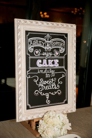 Ornate white chalkboard sign for wedding cake