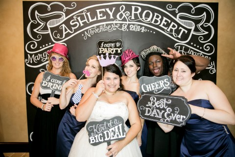 Bride standing with friends in wedding photo booth