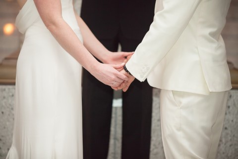 Bride and groom holding hand during wedding ceremony both wearing ivory