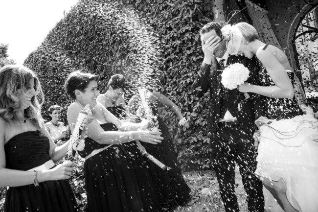 black and white photo of bride and groom having confetti thrown at them