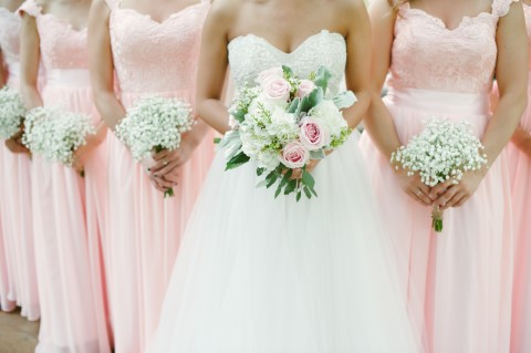 Bride standing with bridesmaids who are wearing pink bridesmaids dresses and holding baby's breath bouquets