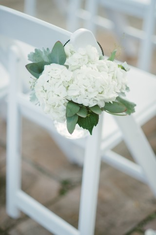 White hydrangeas for wedding aisle decor on white folded chair