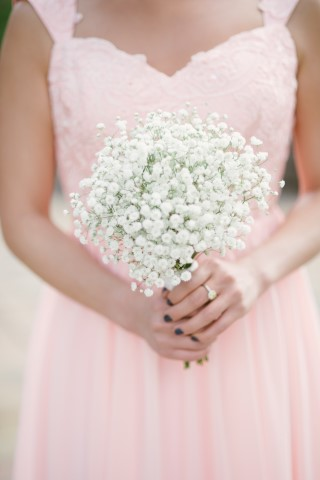 Bridesmaid holding baby's breath bouquet wearing a pink gown