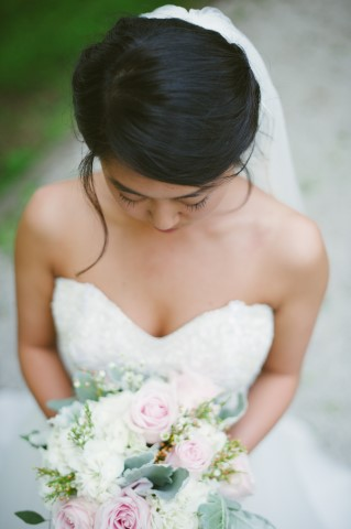 Bride wearing a veil and sweetheart neckline and holding a soft bouquet captured by Ashley West Photography, LLC