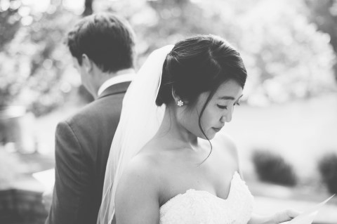 Bride and groom back to back reading letters to each other during their first looks