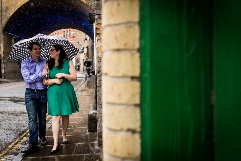 Couple walking with polka-dot umbrella in London for engagement shoot