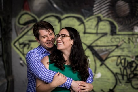 Couple laughing and embracing in front of graffiti wall in London
