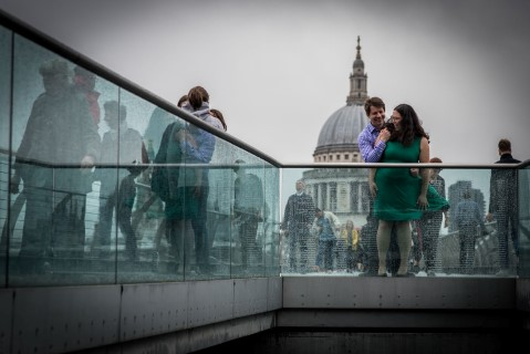 Engaged couple standing in front of St. Paul's Cathedral in the rain and wind