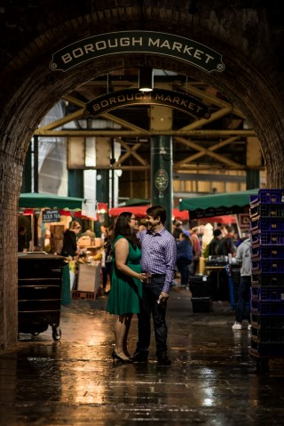 Engagement shoot with couple standing under the borough market sign