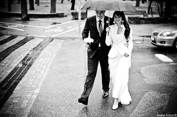 bride wearing light jacket holding umbrella with groom