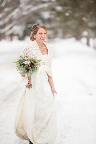 bride wearing knit shawl standing in snow outdoors
