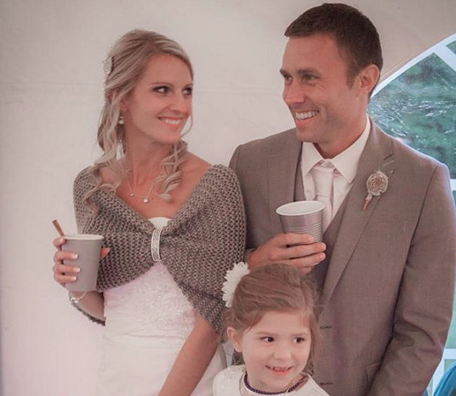 bride in tan color knit shawl standing with groom and flower girl