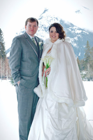 bride wearing warm white cape standing in snow